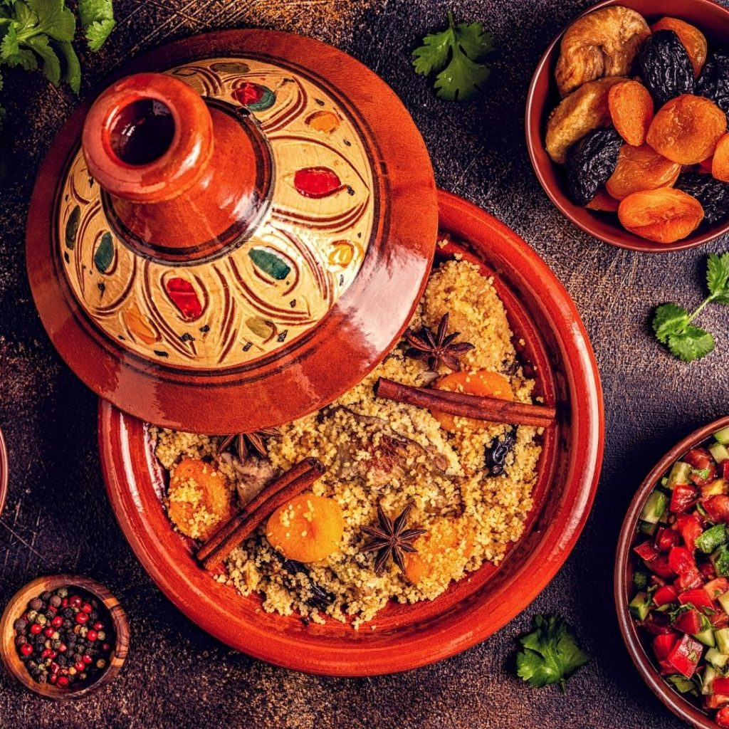 Closeup of Moroccan tagine in traditional pottery with a bowl of dried fruit and spices nearby.
