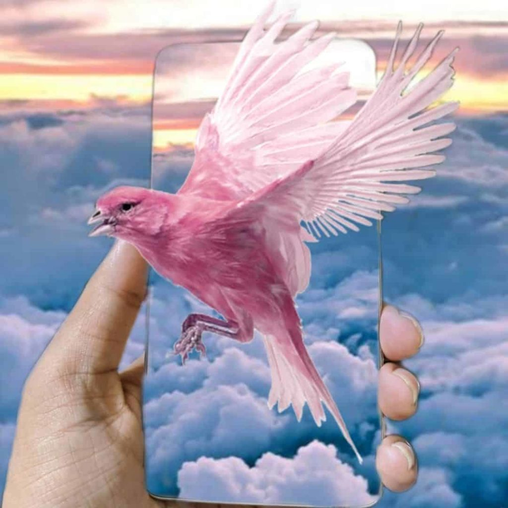 Photo of a surrealistic photo edit with a pink bird appearing to fly out of a mobile phone with clouds in the background.