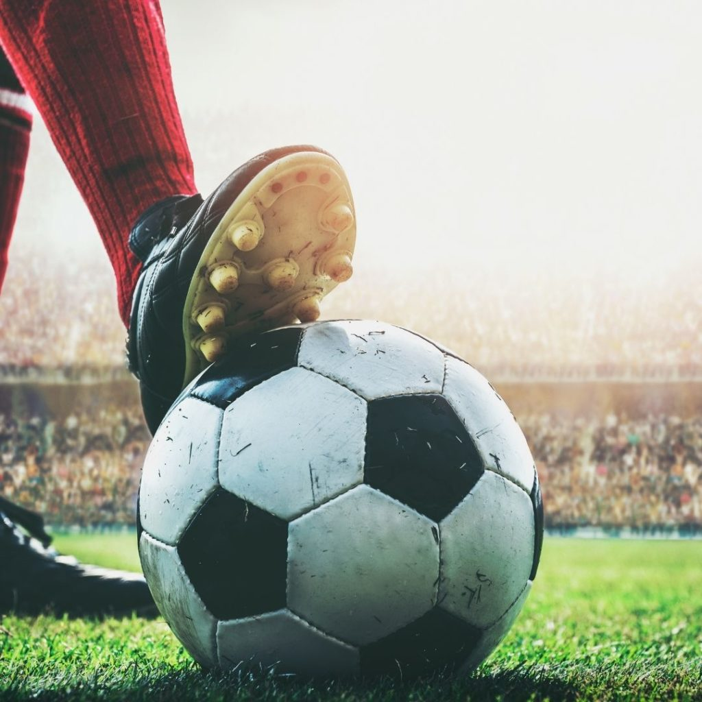 Closeup of a person wearing Soccer cleats with their foot on a Soccer ball.
