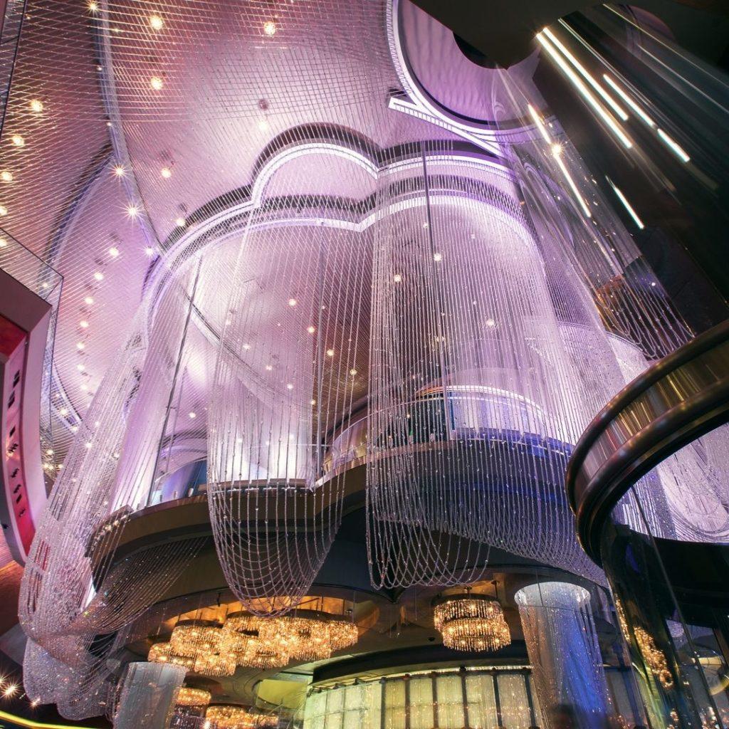 Closeup of the purple-tinged 3 floor chandelier bar at The Cosmopolitan Las Vegas hotel.