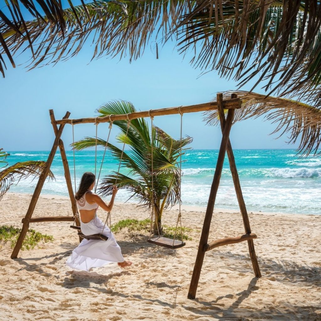 Photo of a woman on a wooden swing on a beach, looking out toward the ocean.