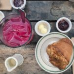 Flatlay photograph of a popover from Jordan Pond House and a glass of blueberry lemonade.