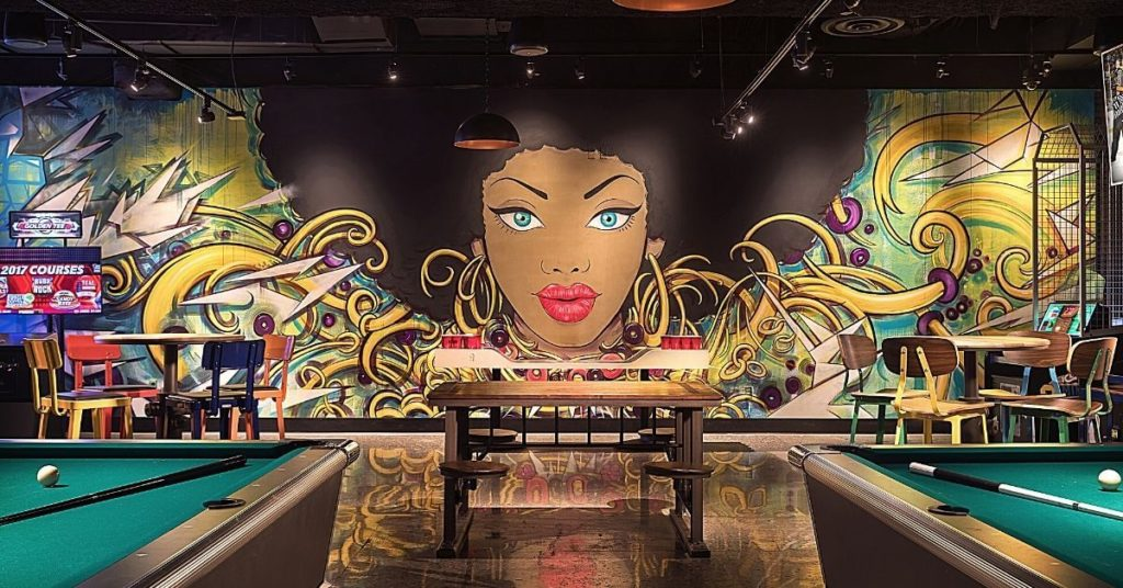 Photo of the interior of the Level Up lounge at MGM Grand with pool tables, arcade games, and street art style artwork.
