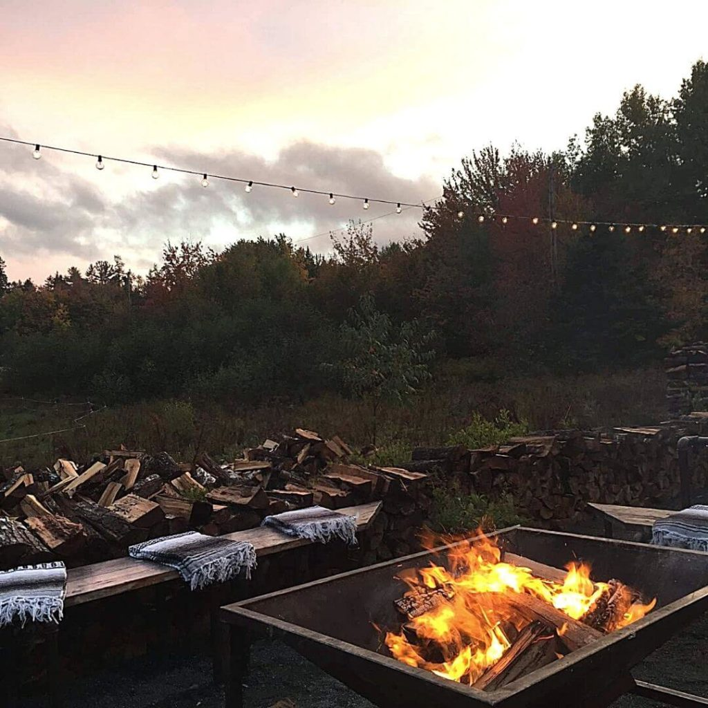 Snapshot of a firepit with benches set around it. In the background are piles of wood, trees, and outdoor string lights.