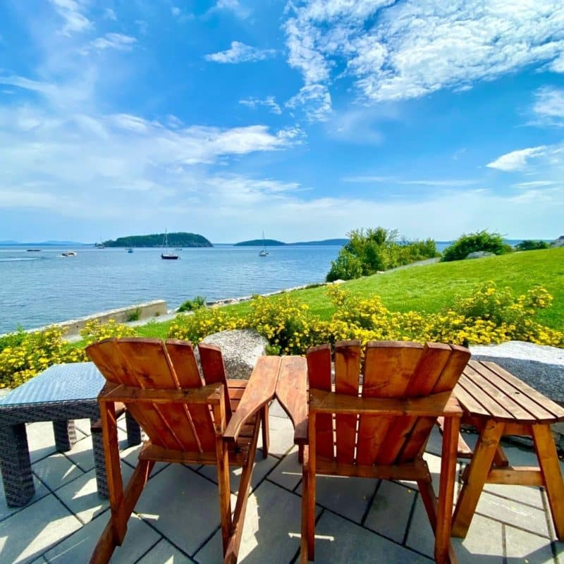 Closeup of 2 adirondack chairs overlooking Frenchman Bay in Bar Harbor, Maine.