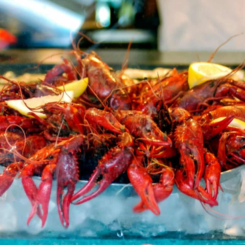 Closeup of a tray of crawfish with lemon wedges.