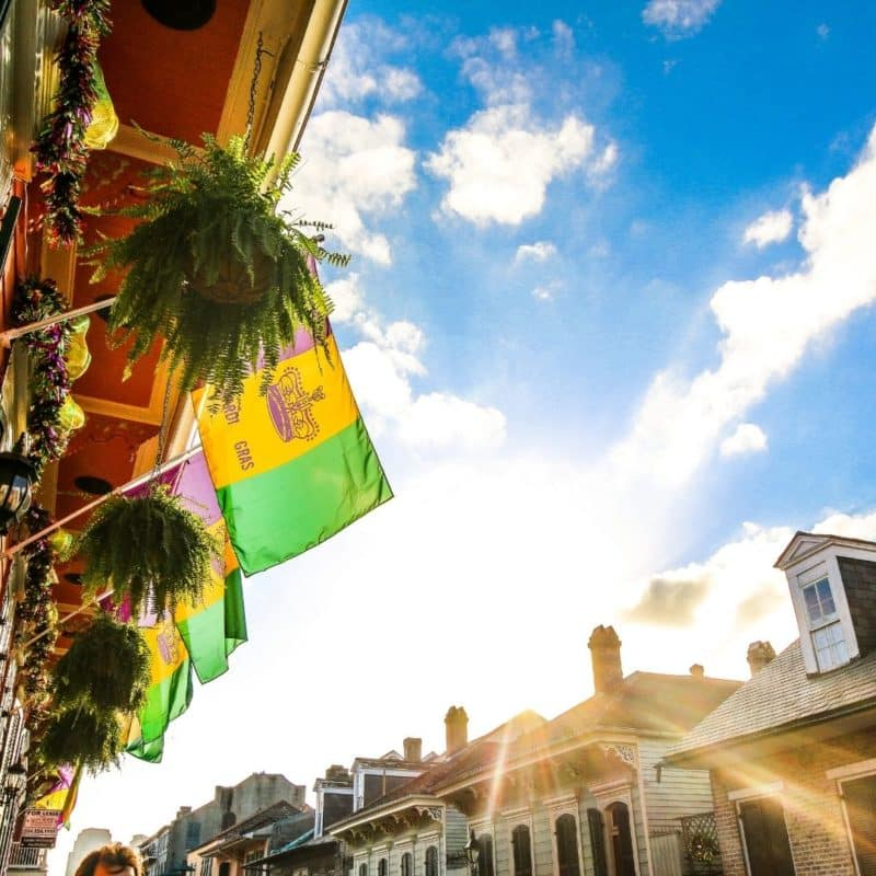 Closeup of purple, gold, and green Mardi Gras flags hung off of a New Orleans balcony.