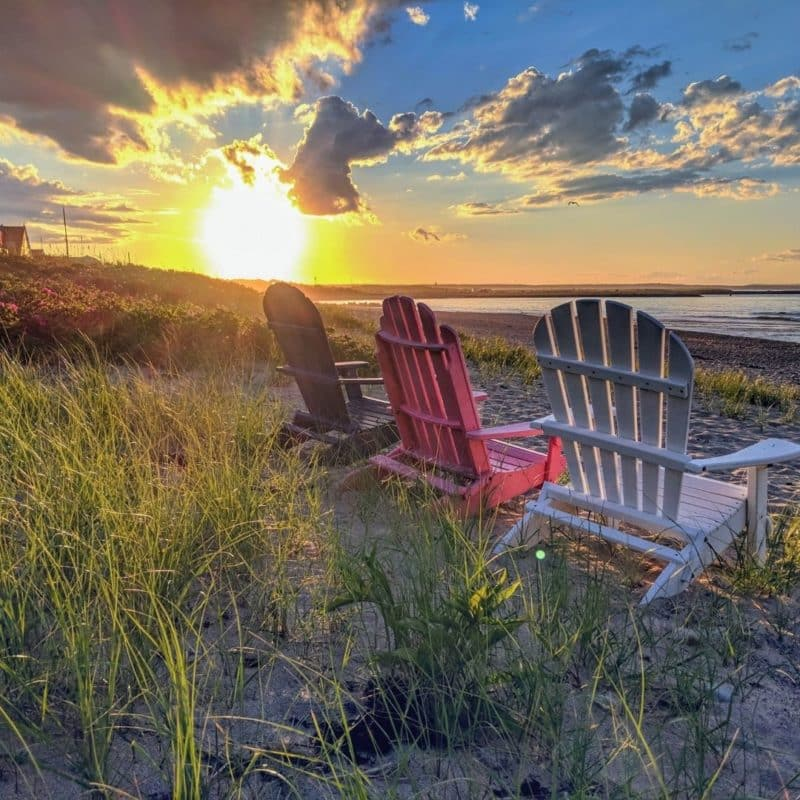 Closeup of 3 empty Adirondack-style chairs sitting on a beach overlooking the sun as it sets over the Atlantic ocean from a Cape Cod beach.
