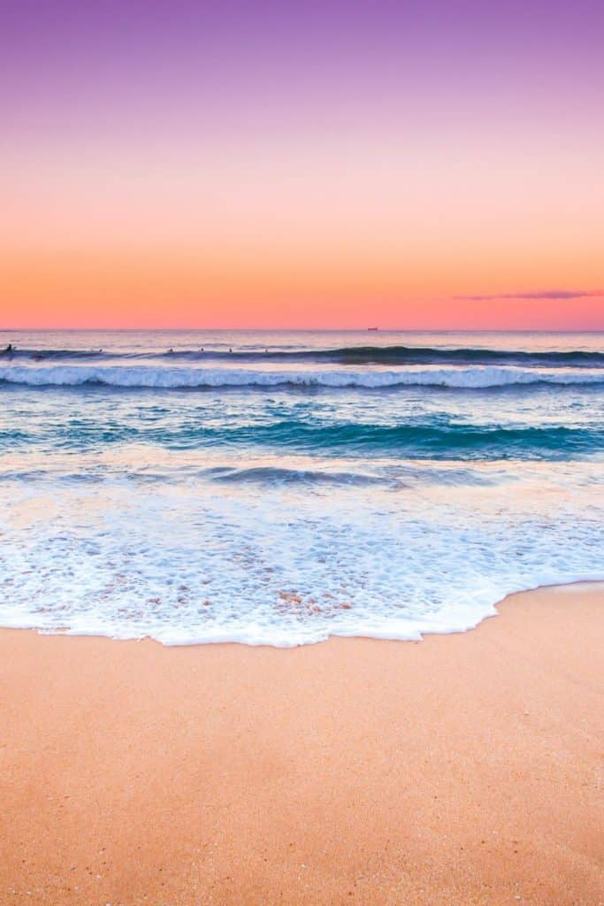 Photo of a beach at sunset with purple, pink, and orange sky.
