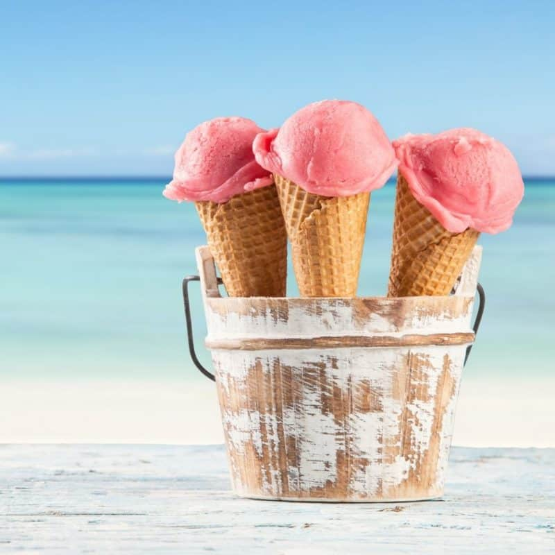 Photo of 3 ice cream cones with bright pink ice cream sitting in a wooden bucket with the beach in the background.