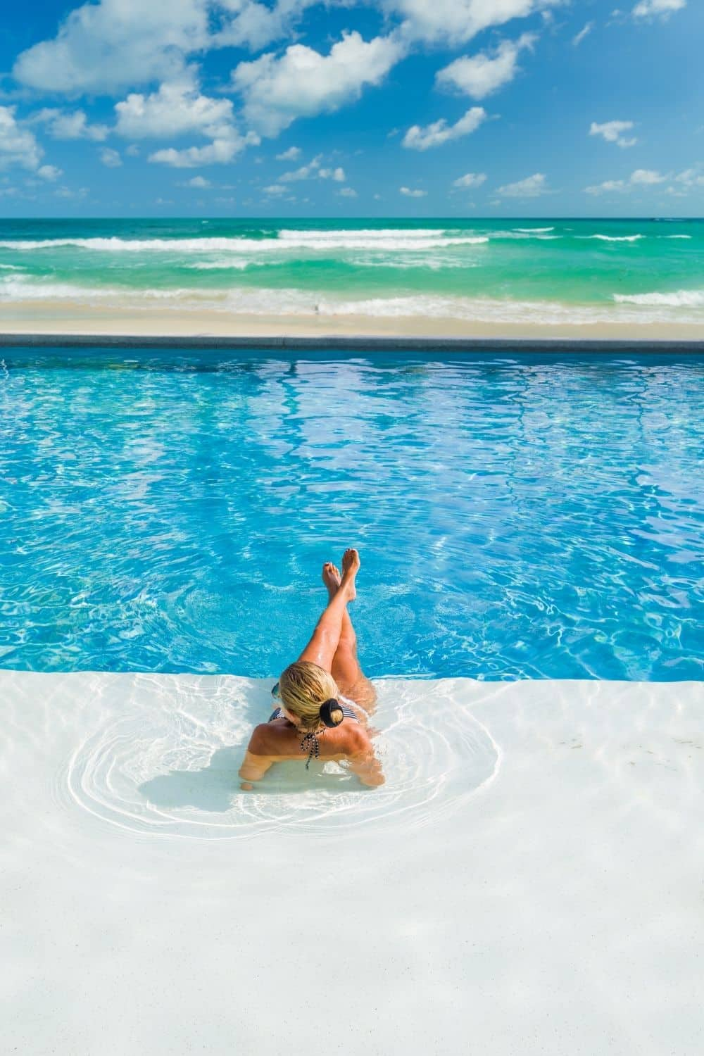 Photo of a woman lounging in a pool overlooking the ocean.