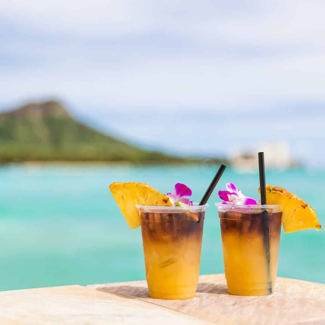 Photo of 2 mai tai cocktails sitting on a ledge with the Hawaiian shoreline in the background.