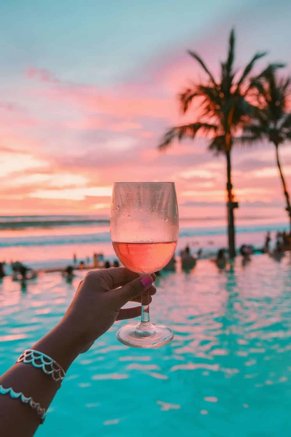 Photo of a woman holding up a glass of rose wine in front of a pool overlooking the Hawaiian shoreline during sunset.