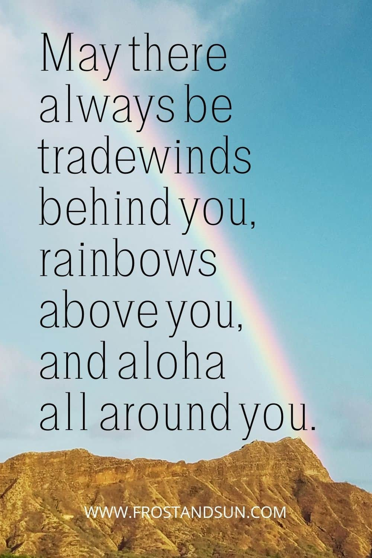 Photo of a rainbow reaching down toward a mountain in Hawaii.