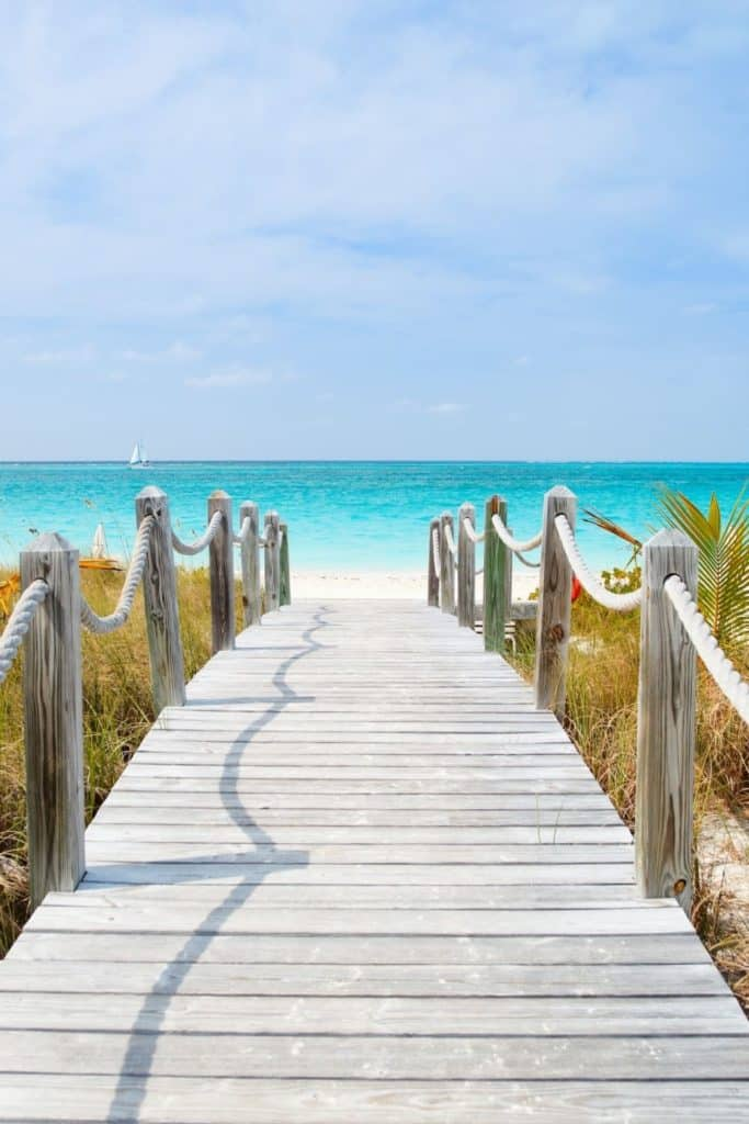 Photo of a wooden walkway leading down to a beach.