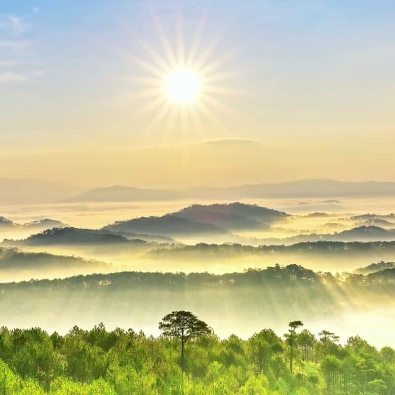 Photo of the sun rising over a plush green valley and mountains in the background.