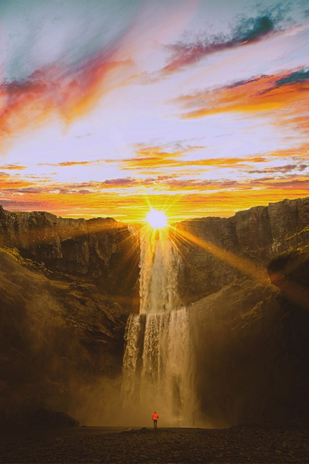 Photo of the sun setting behind giant mountains with a waterfall.
