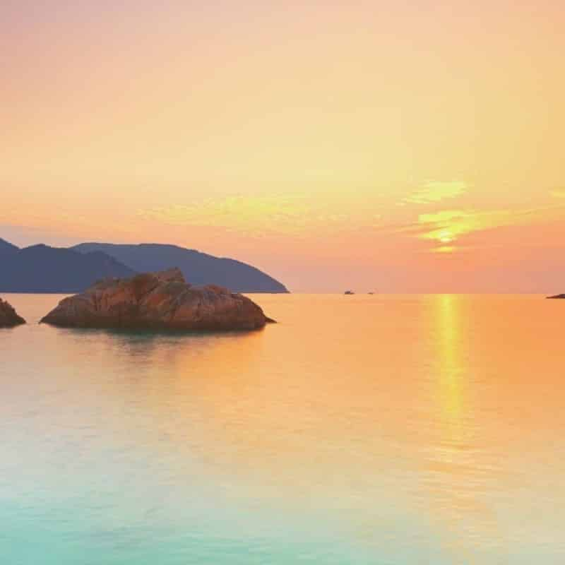 Photo of a candy-colored sunset view with the ocean in the foreground and mountains in the background.
