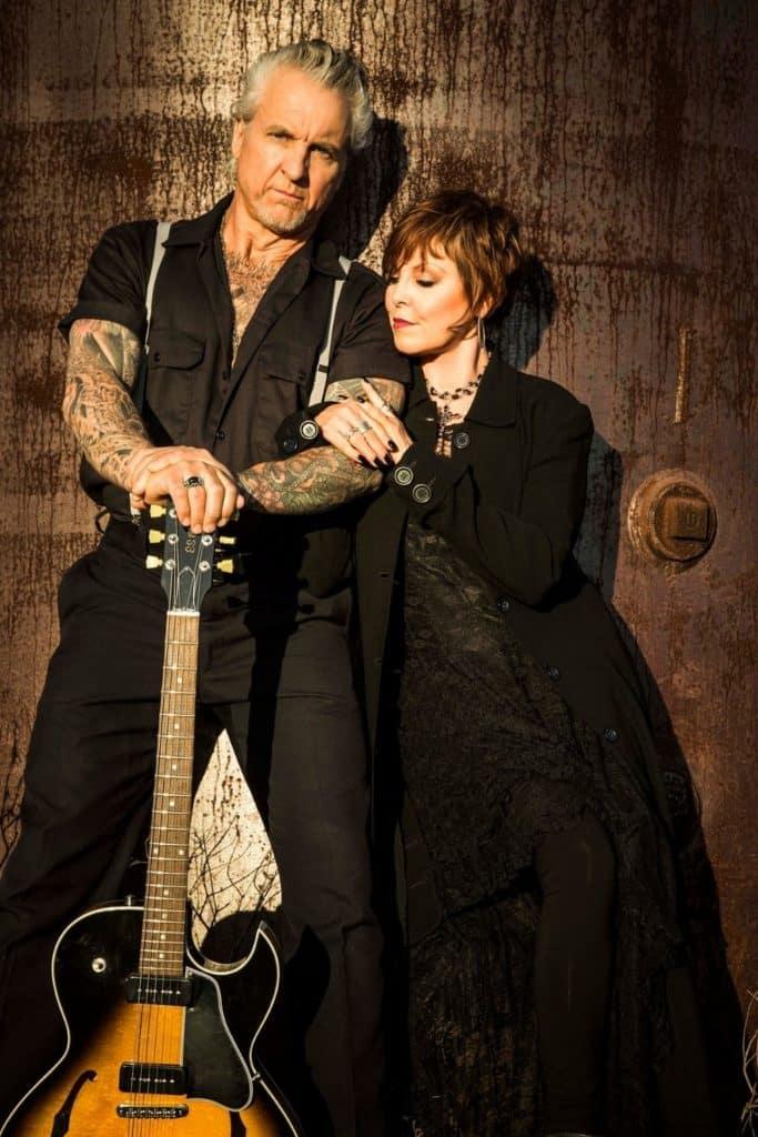 Press photo of musicians Pat Benatar and Neil Giraldo posing with a guitar.
