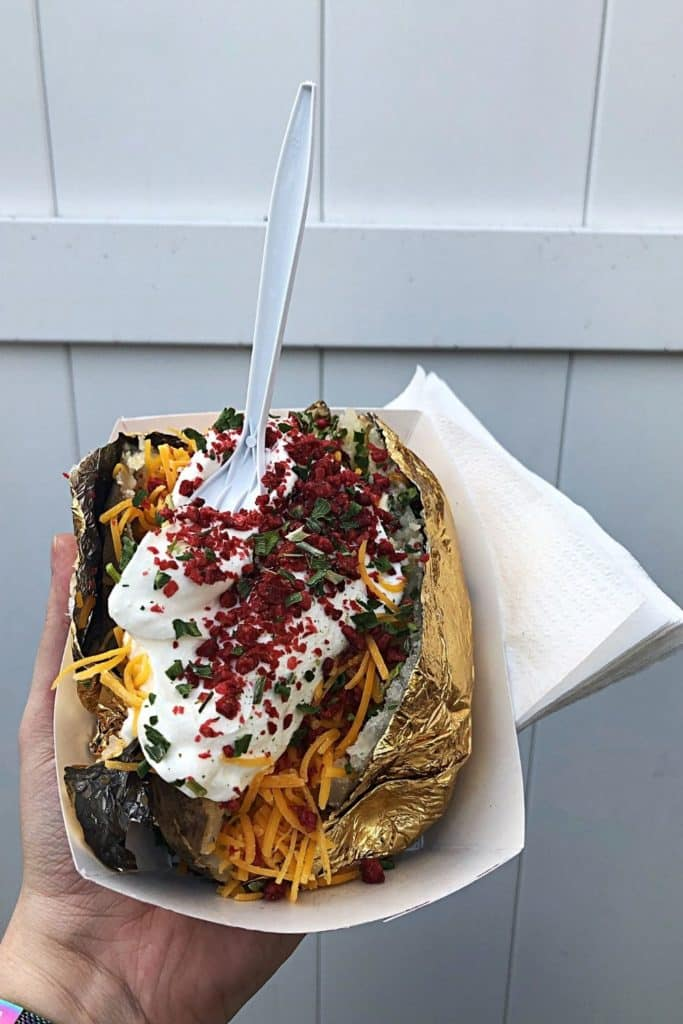 Closeup of a massive Maine baked potato topped with shredded cheddar cheese, sour cream, bacon, and chives.