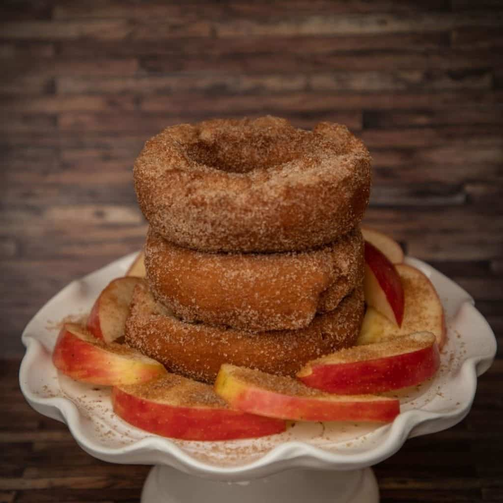 Closeup of a stack of 3 apple cider donuts with apple slices arranged around them on a white pedestal platter.