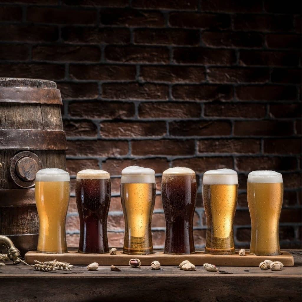 Closeup of a beer tasting board with 6 pints of beer.