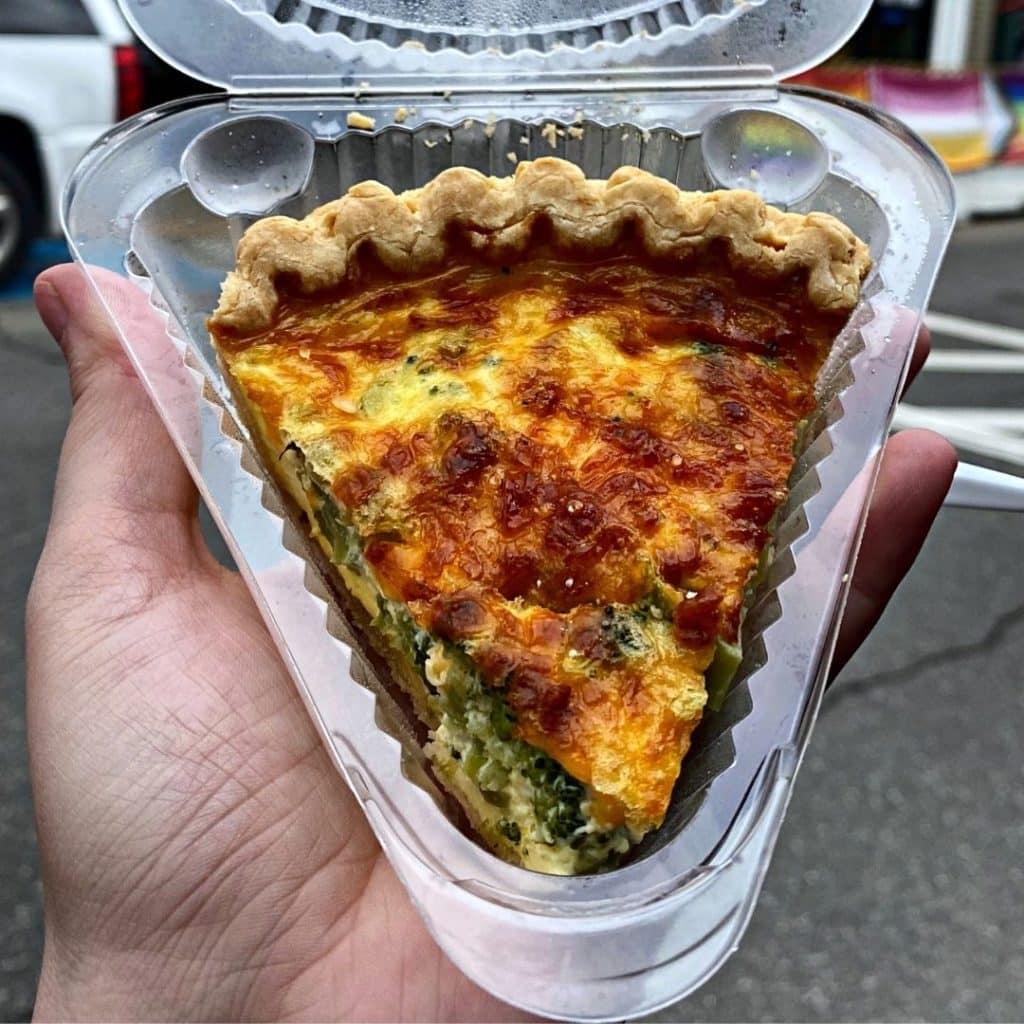 Closeup of Broccoli Cheddar Quiche in a to-go container.