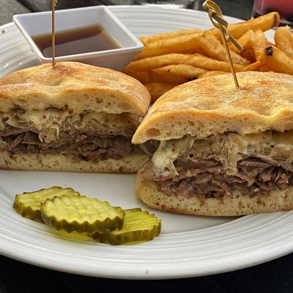 Closeup of the Dublin pub dip sandwich with ribeye beef, carmelized onions, and horseradish cream. Golden crispy fries and aus jus dip are placed behind the sandwich and a stack of pickle chips are in front.