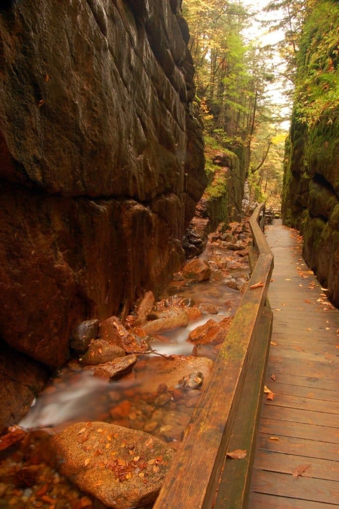 Photo of the wooden walkway along the Flume Gorge Trail in New Hampshire in the Fall with orange and brown leaves on the ground.