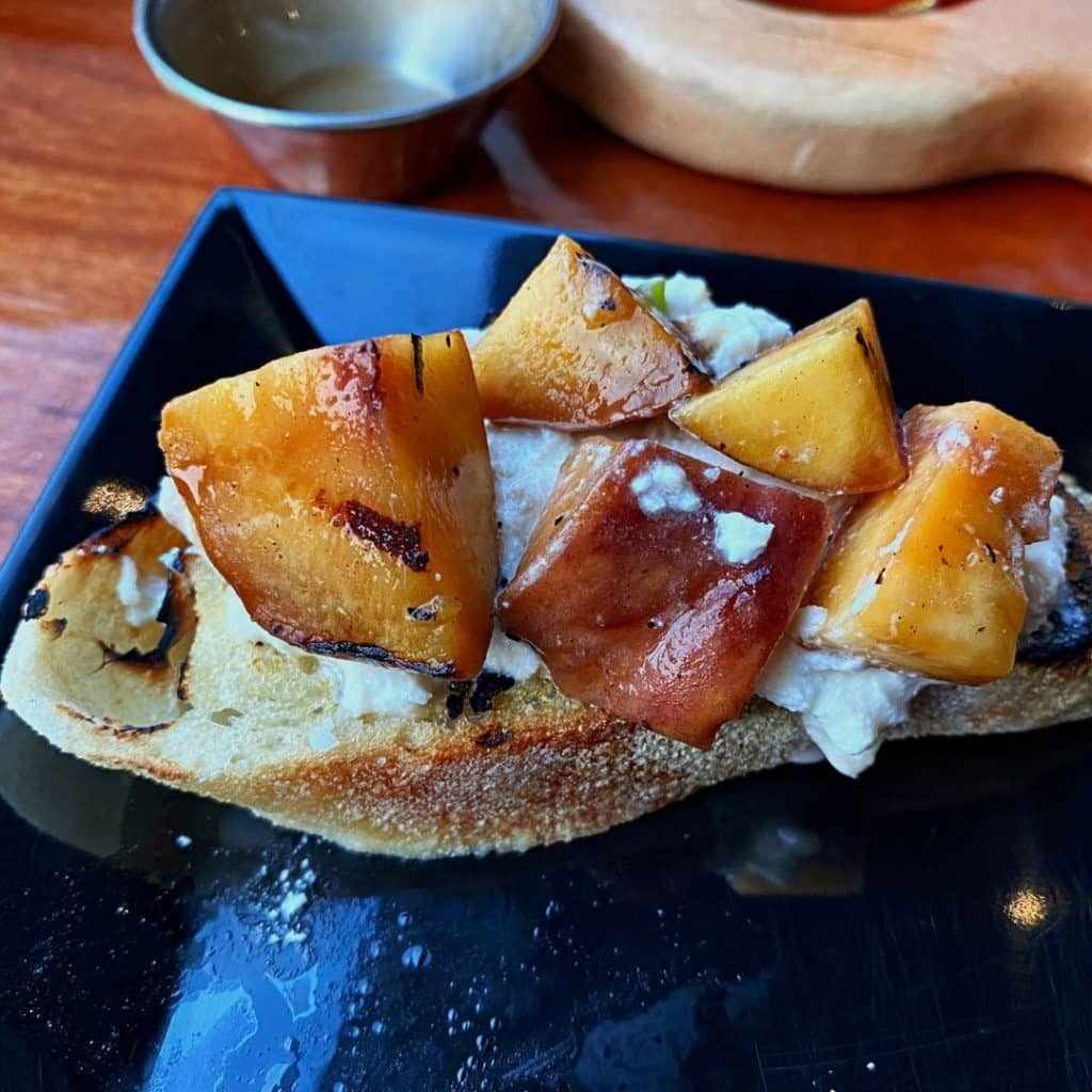 Closeup of toast with smoked burrata mozzarella cheese and grilled peaches on top.
