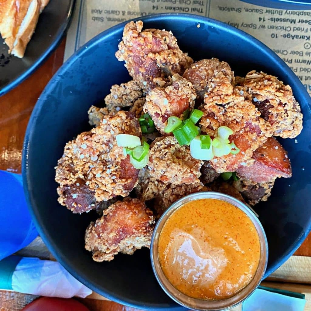 Flat lay view of a bowl of Japanese fried chicken thigh bites with a spicy sauce in a cup.