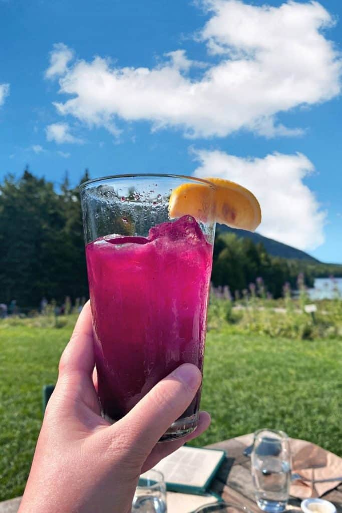 Hand holding a tall glass of blueberry lemonade in front of the Bubbles mountains at Jordan Pond House.