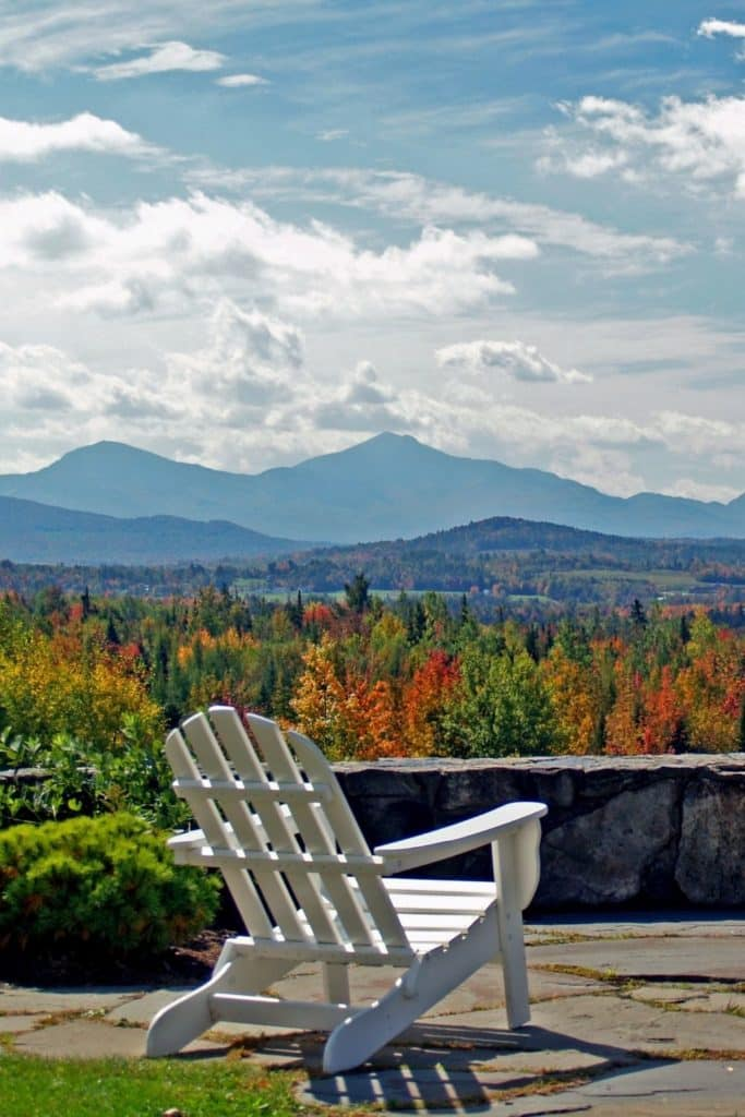 Photo of a white Adirondack chair overlooking a valley filled with Fall foliage from the Mountain View Grand Resort in New Hampshire.