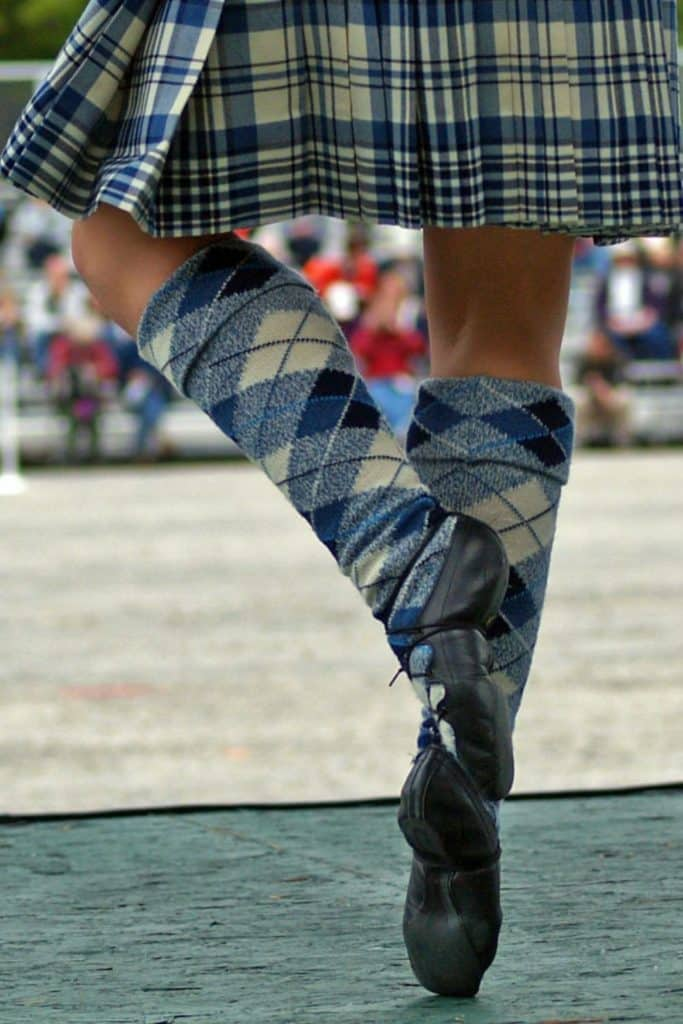 Closeup from behind of a woman performing Scottish folk dancing while dressed in blue plaid and argyle.