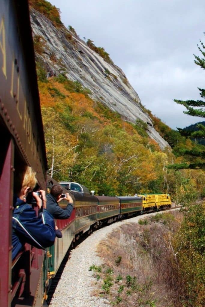 Photo of a train rounding a curve with passengers leaning out the window to capture photos of the Fall foliage.