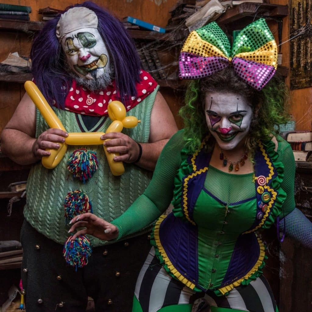 Photo of 2 creepy clowns dressed in green, yellow, and purple.