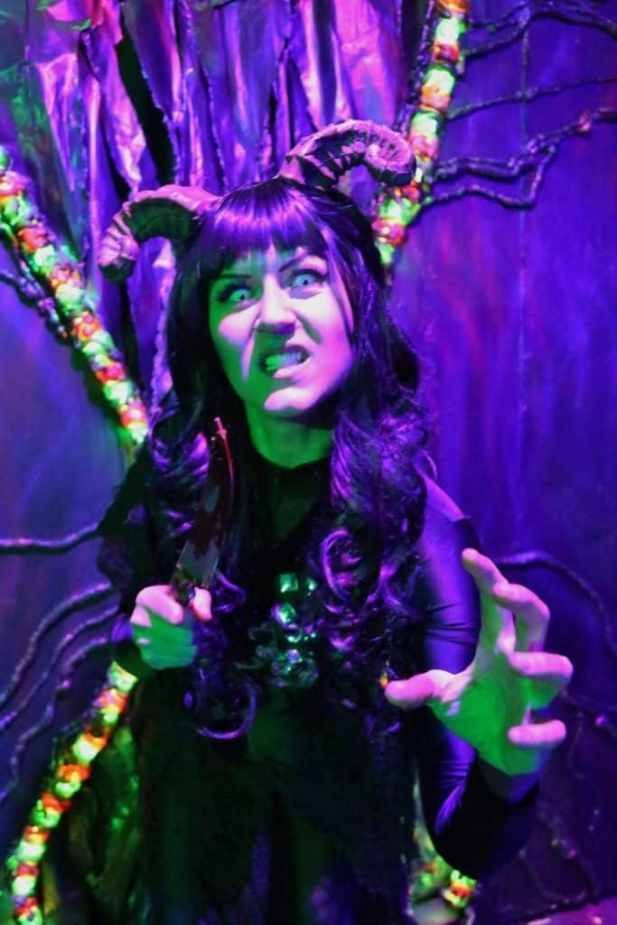 Photo of a woman with horns attached to her head in an intimidating pose. The entire photo is lit up with a purple hue.