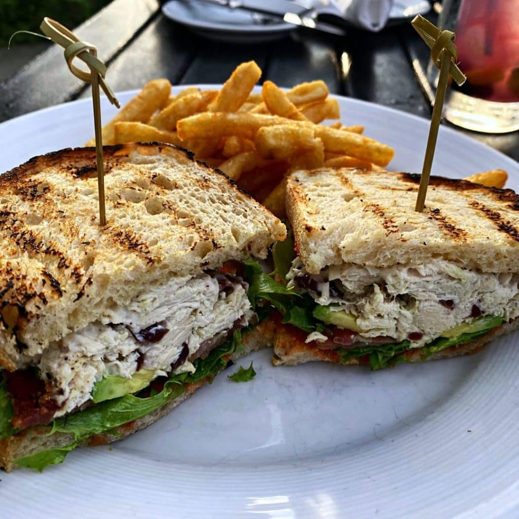 Closeup of a sandwich cut in half and stuffed with rotisserie chicken, avocado, bacon, and lettuce, with crispy golden french fries behind the sandwich.