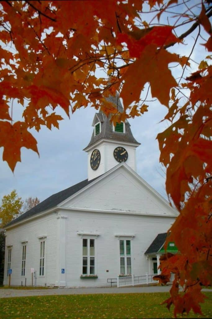 Photo of a white church in Sugar Hill, NH with Autumn leaves framing the photo.