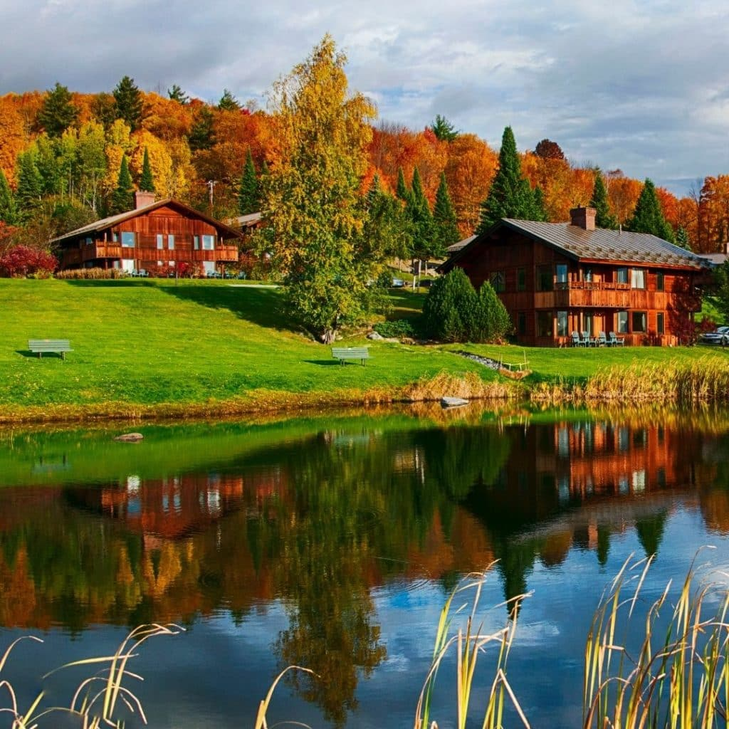 Landscape view of the Trapp Family Lodge with a pond in the foreground, and several lodges and cabins set against Fall foliage in the background.