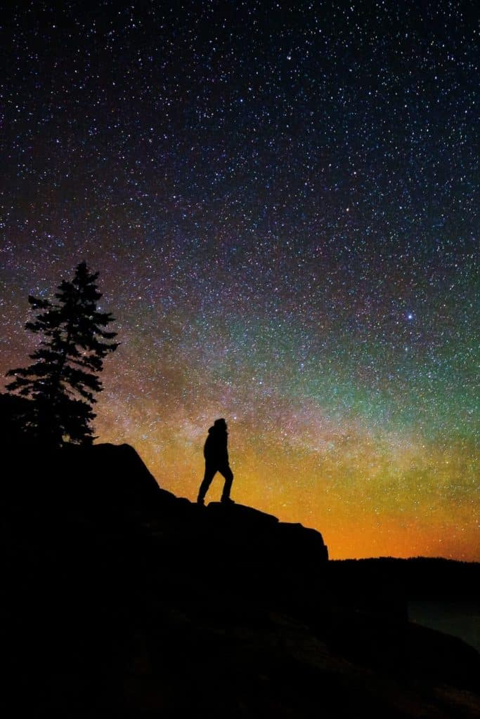 Photo of a silhouette of a man and a tree on a cliff against a starry sky with colors of orange, green, purple, and blue.
