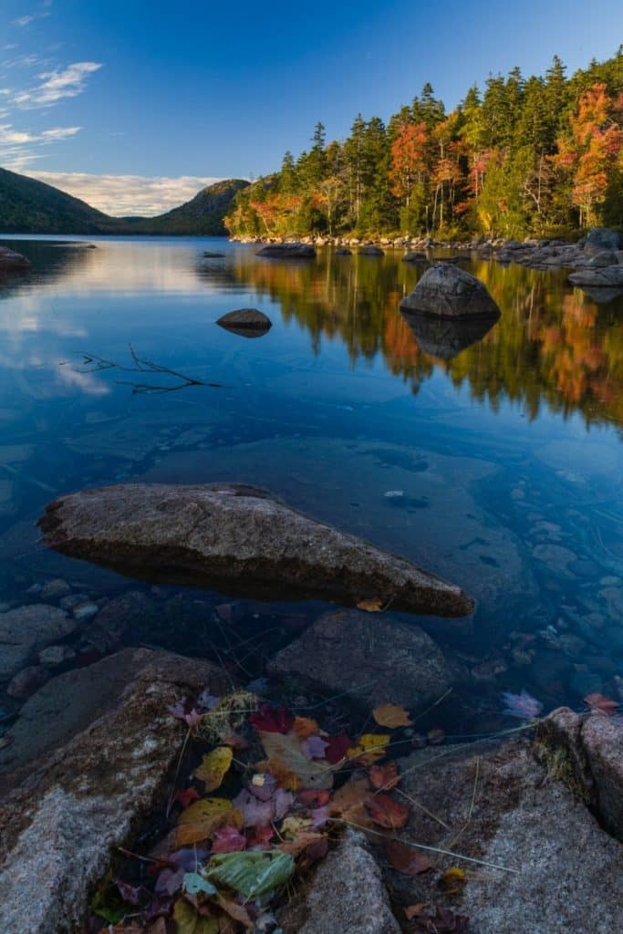 Photo of Jordan Pond in Acadia National Park with Fall foliage along the shore, reflecting in the pond.