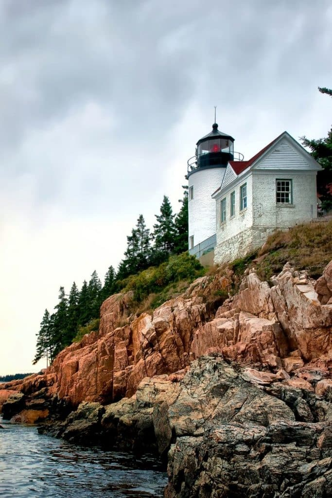 Photo of a bright white lighthouse perched on a rocky cliff.