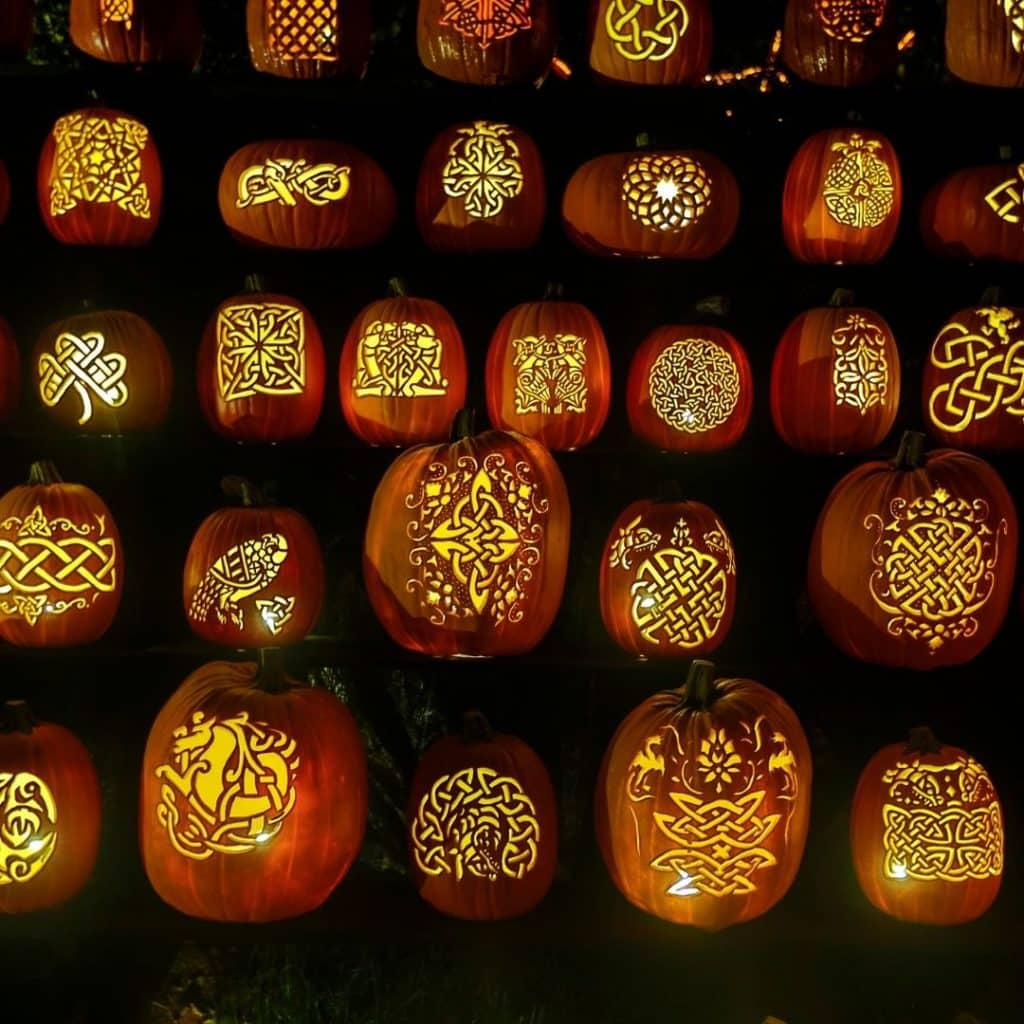 Photo of pumpkins with celtic knots carved into them, lit up from the inside.