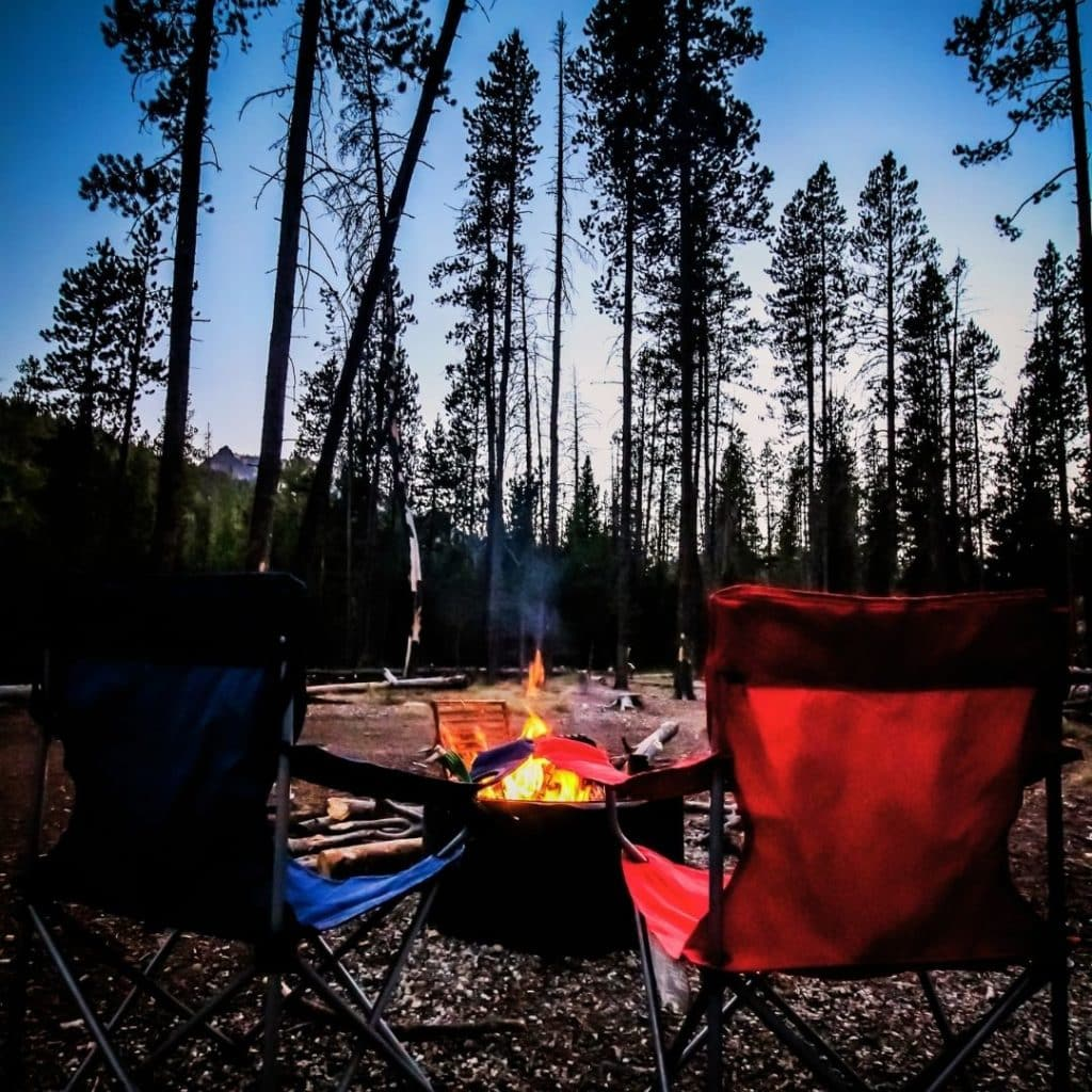 Photo of a bonfire with 2 camping chairs for kids in the foreground.