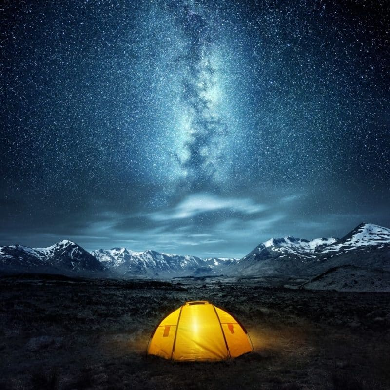 Photo of a yellow tent in the middle of an open field with mountains and a starry sky with the Milky Way galaxy in the background.