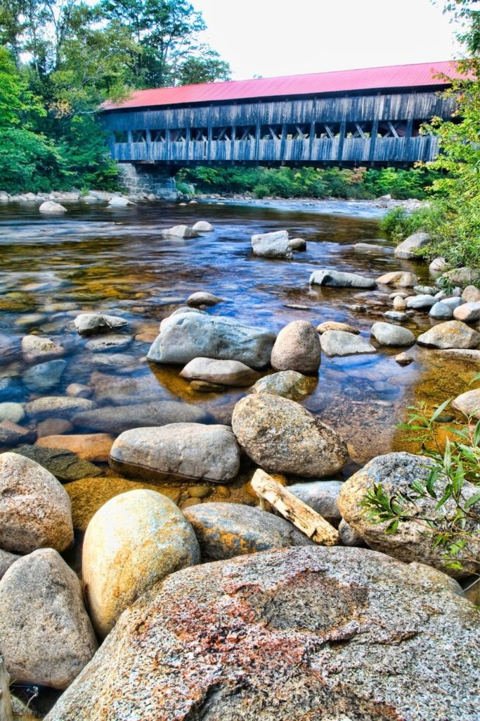 Photo of an old covered bridge in New Hampshire with a creek and rocks in the foreground.