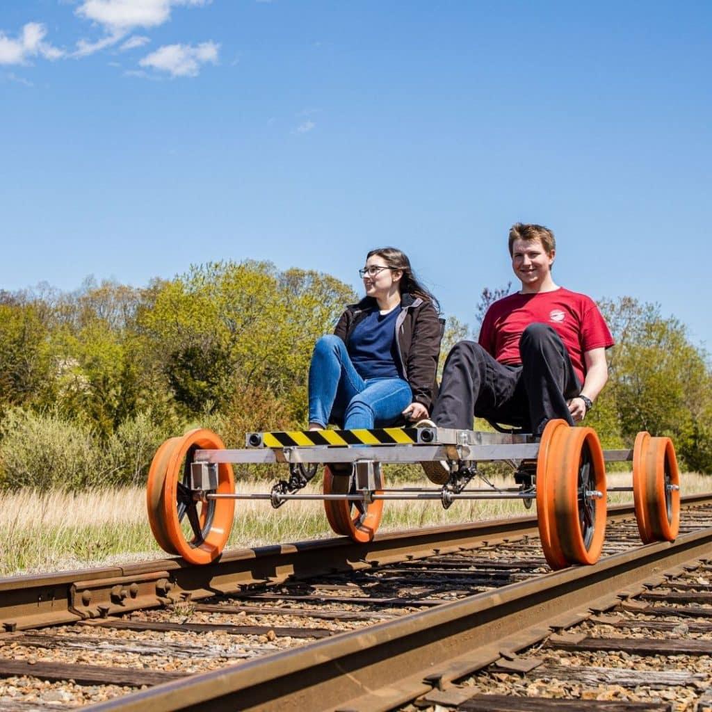 Photo of a man and woman pedaling a rail bike.
