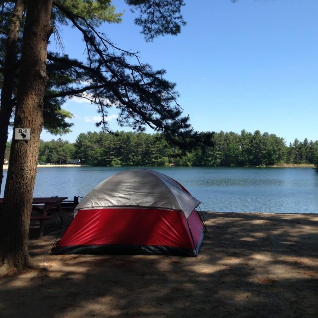 Photo of a camping tent set up on a lakeside beach.