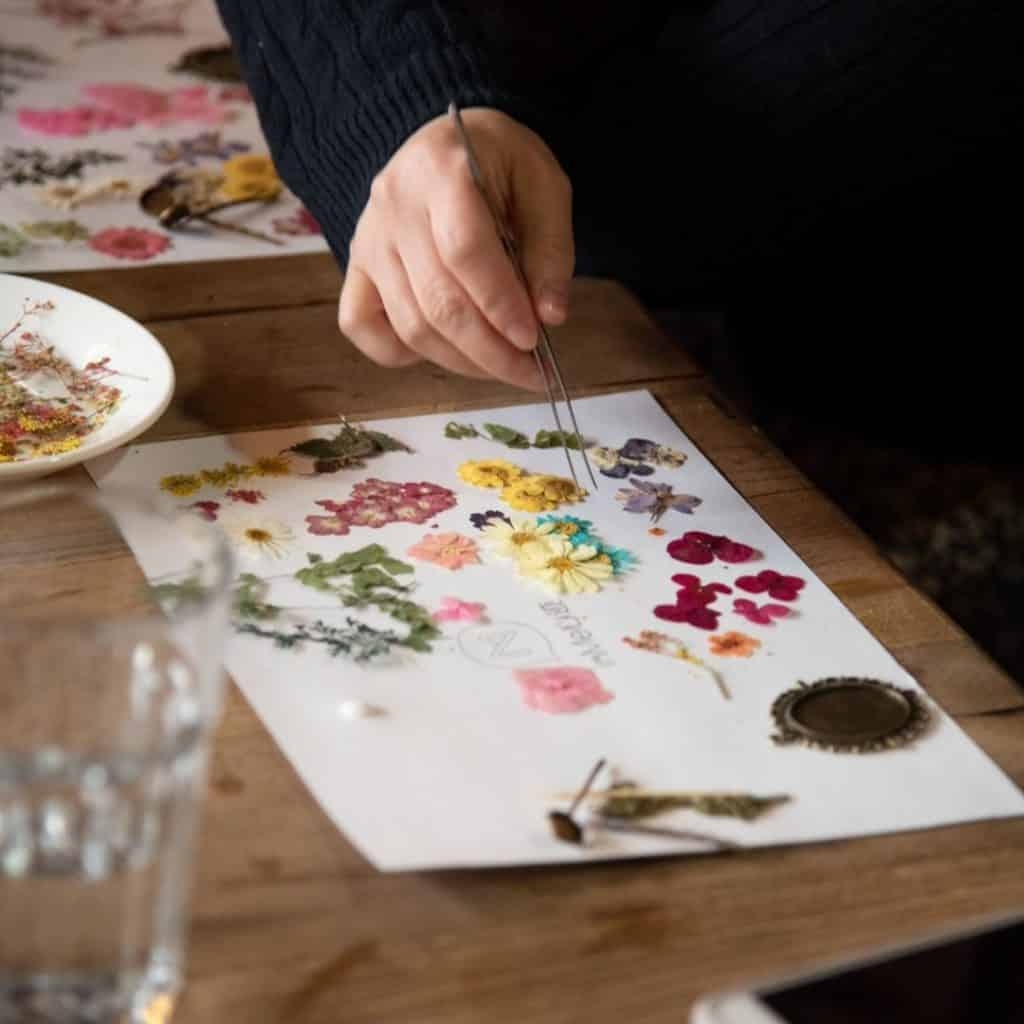 Closeup of someone creating a picture using pressed flowers.